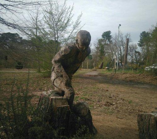 Statue taillée à la tronçonneuse dans une souche et représentant un footballeur