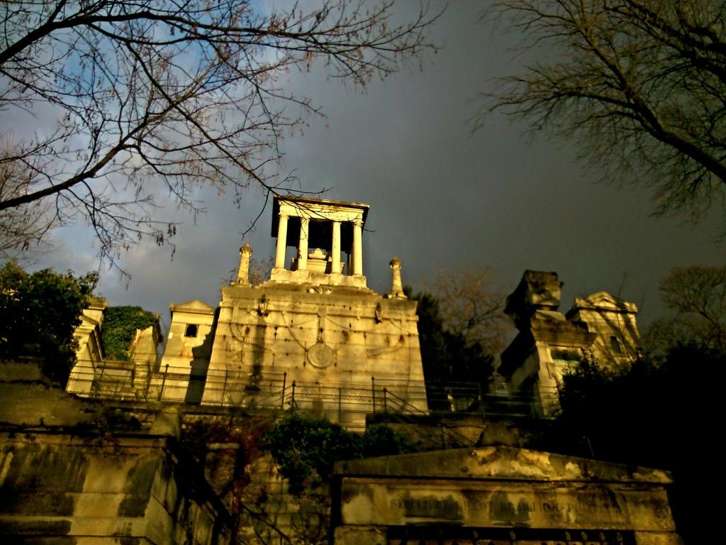 Une tombe du Père Lachaise, en contre-plongée, éclairage dramatique.